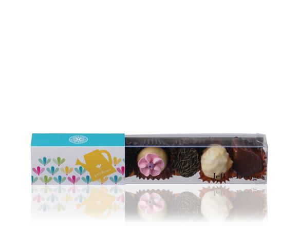Průhledná krabička obsahuje výběr čokoládových bonbonů, z nichž i naši novinku hruškovou ganáž a marcipán s čokoládou ve tvaru kytičky.